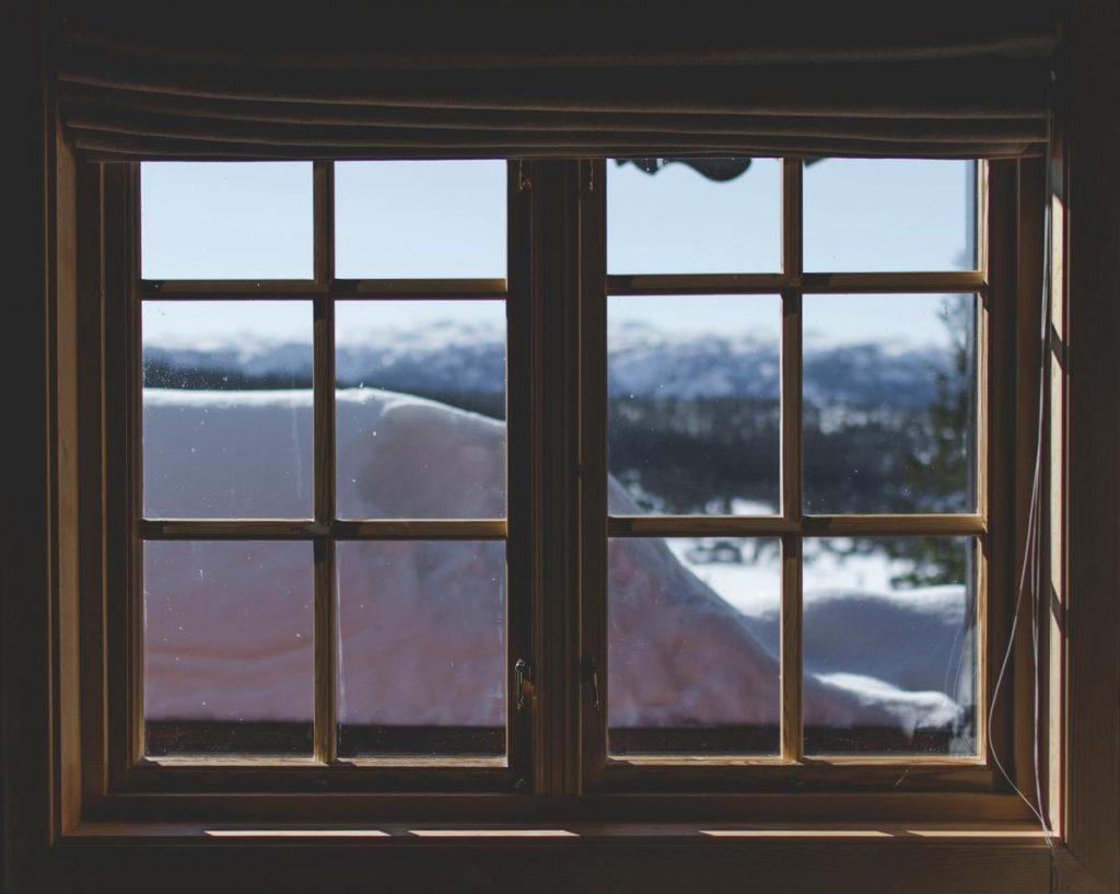 fenêtre en bois d'une maison de jeux donnant sur de la neige