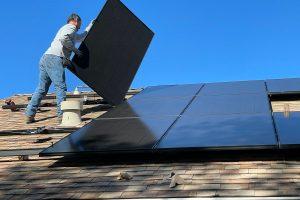 homme installant des panneaux solaires sur le toit de sa maison